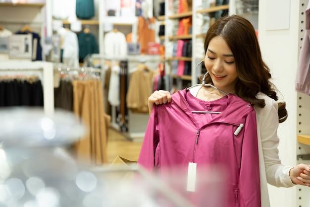 Piękna uśmiechnięta azjatycka kobieta robi zakupy w sklepie odzieżowym i wybiera różowy sweter z cieszy się podekscytowana gorącą wyprzedażą końca sezonu w centrum handlowym