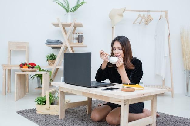 Piękna uśmiechnięta azjatycka studentka ucząca się z internetowej usługi edukacyjnej, młoda azjatka odrabiająca zadanie domowe pijąca filiżankę kawy