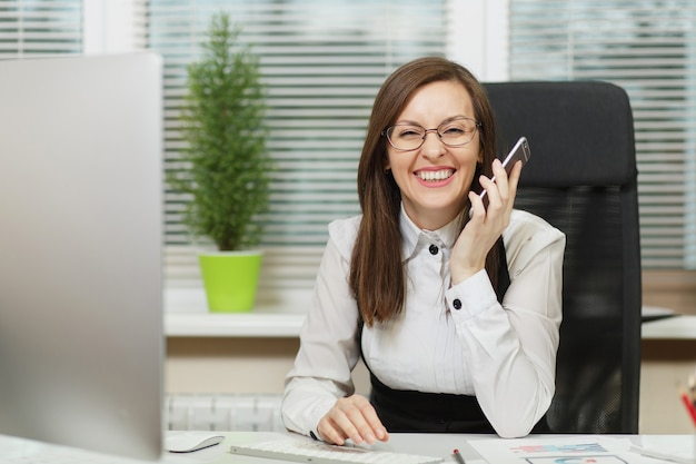 Piękna uśmiechnięta biznesowa kobieta w garniturze i okularach siedząca przy biurku, pracująca przy współczesnym komputerze z dokumentami w jasnym biurze, rozmawiająca przez telefon komórkowy, prowadząca przyjemną rozmowę