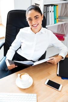 Piękna uśmiechnięta bizneswoman czyta dokumenty siedząc przy biurku i patrząc na przód