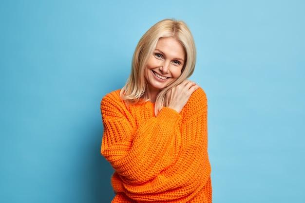 Piękna uśmiechnięta blondynka obejmuje się, wygląda z czułym, zadowolonym wyrazem przechyla głowę i nosi ciepły sweter z dzianiny.