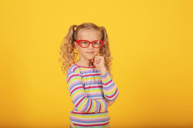 Piękna uśmiechnięta blondynka w okularach na żółtym tle w kolorowej kurtce emocje