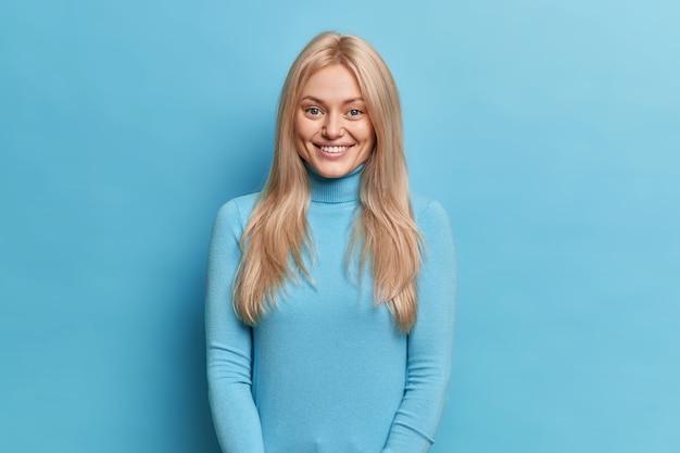 Piękna uśmiechnięta blondynka wyraża radość, gdy ktoś się cieszy, ma uroczy, przyjazny wyraz twarzy ubrany w swobodny golf