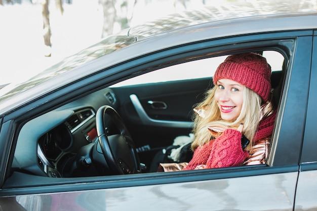 Piękna uśmiechnięta blondynka z czerwoną czapką i szminką siedzi na siedzeniu kierowcy w samochodzie