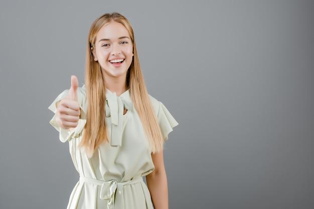 Piękna uśmiechnięta blondynki dziewczyna pokazuje aprobaty odizolowywać