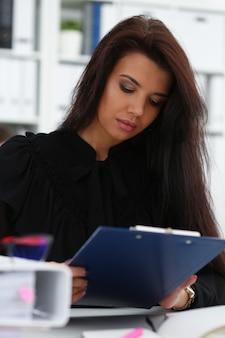 Piękna uśmiechnięta brunetka kobieta trzyma w ramionach różowy długopis i papier przypięty do podkładki na sobie portret stylowe okulary.