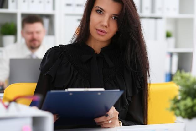 Piękna uśmiechnięta brunetka kobieta trzyma w ramionach różowy długopis i papier
