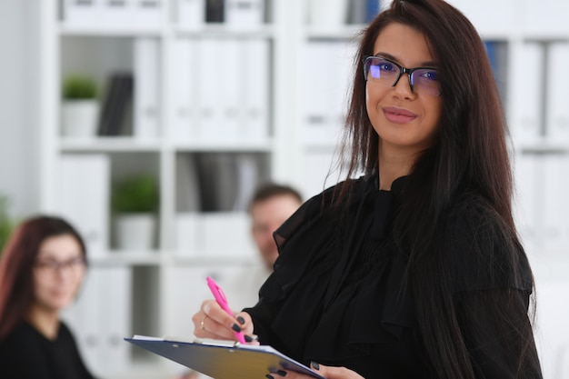 Piękna uśmiechnięta brunetka kobieta trzyma w ramionach różowy długopis