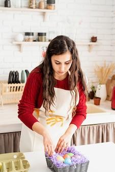Piękna uśmiechnięta brunetka kobieta w czerwonym swetrze i białym fartuchu ozdabia kolorowe pisanki