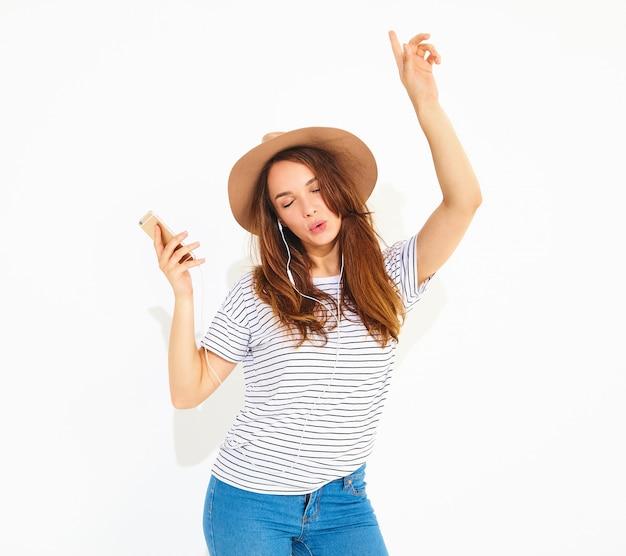 Piękna uśmiechnięta brunetka kobieta w dorywczo hipster letnie ubrania bez makijażu w brązowy kapelusz słuchania muzyki w telefonie ze słuchawkami na białym tle
