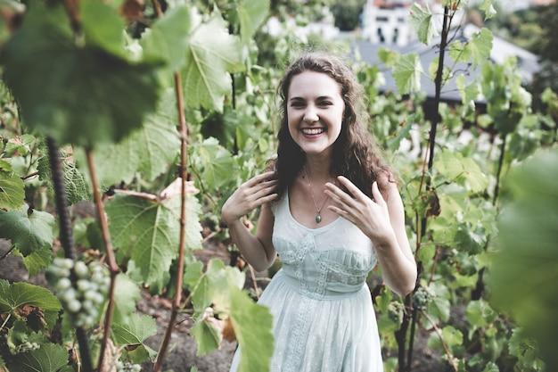 Piękna uśmiechnięta brunetka kręcone włosy w jasnoniebieskiej prostej sukni w winnicy