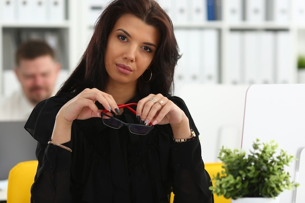 Piękna uśmiechnięta brunetka siedzi przy stole roboczym