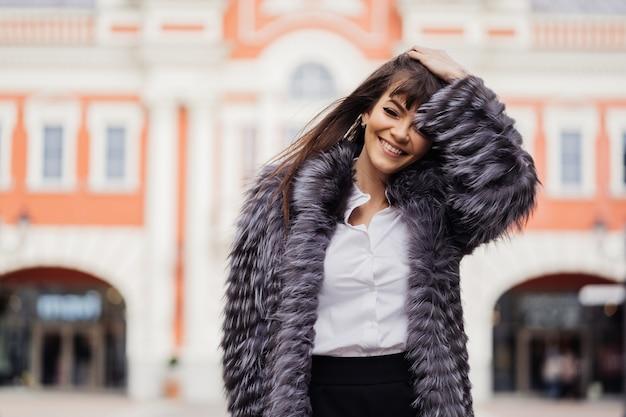 Piękna uśmiechnięta brunetka z długimi prostymi włosami ubrana w futro na tle budynku w stylu klasycznym
