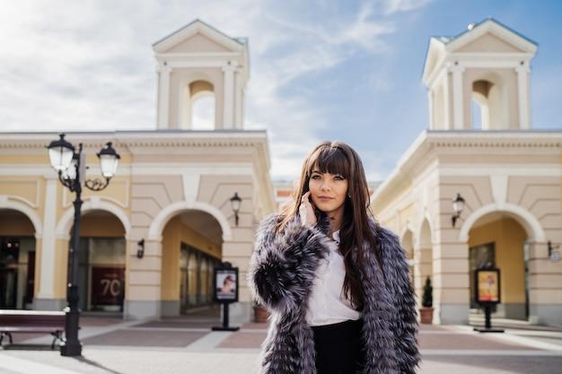 Piękna uśmiechnięta brunetka z długimi prostymi włosami w futrze i białą spódnicą stojącą na tle budynku w stylu klasycznym