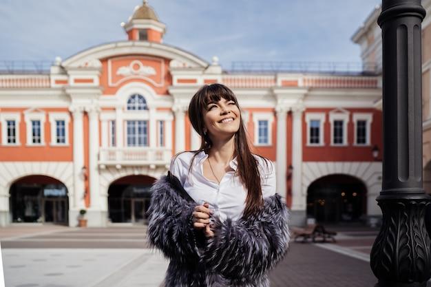 Piękna uśmiechnięta brunetka z długimi prostymi włosami w futrze i białą spódnicą stojącą na tle klasycznego budynku uśmiecha się, patrząc na słoneczne błękitne niebo