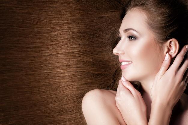 Piękna uśmiechnięta brunetka ze zdrowymi długimi włosami