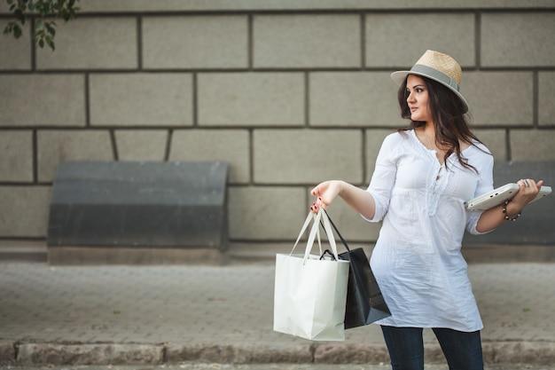 Piękna uśmiechnięta brunetki dziewczyna w kapeluszu chodzi w dół ulicę z laptopem i pakunkami od sklepu.