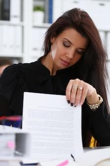 Piękna uśmiechnięta brunetki kobieta siedzi przy stołem