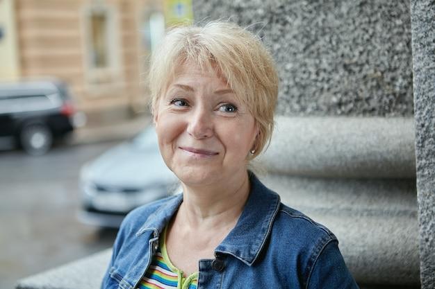 Piękna uśmiechnięta dojrzała kobieta z krótkimi blond włosami pozuje na ulicy miasta.
