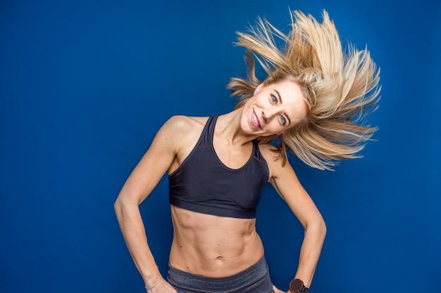 Piękna uśmiechnięta dysponowana młoda kobieta w sportowym staniku z bieżącym włosy. taniec, siłownia, szczupła koncepcja