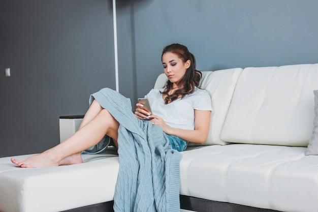 Piękna uśmiechnięta dziewczyna azjatyckich szczupła młoda kobieta siiting na kanapie i za pomocą telefonu komórkowego, odpoczynek w domu