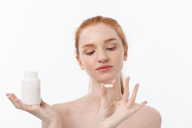 Piękna uśmiechnięta dziewczyna biorąc leki, trzymając butelkę z pigułkami. zdrowa szczęśliwa żeńska łasowanie pigułka. witaminy i suplementy, pojęcie diety