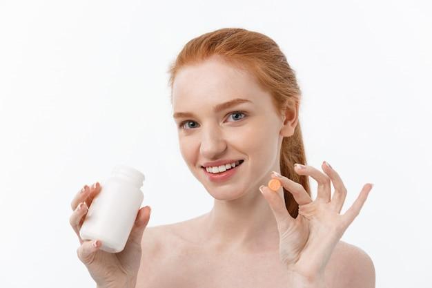 Piękna uśmiechnięta dziewczyna biorąc leki, trzymając butelkę z pigułkami.