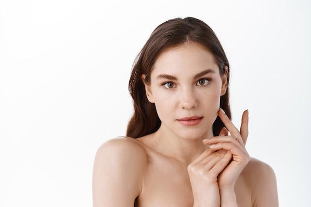 Piękna uśmiechnięta dziewczyna modelka z naturalnym makijażem dotykająca świecącej nawilżonej skóry na białej ścianie zbliżenie