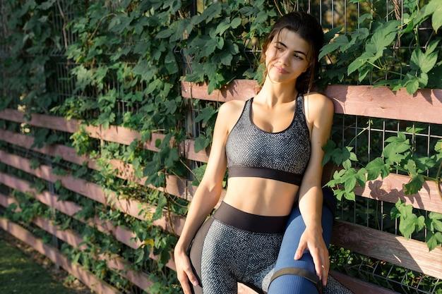 Piękna uśmiechnięta dziewczyna na siłowni rano w parku.