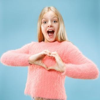 Piękna, uśmiechnięta dziewczyna nastolatka sprawia, że kształt serca z rękami na niebieskiej ścianie