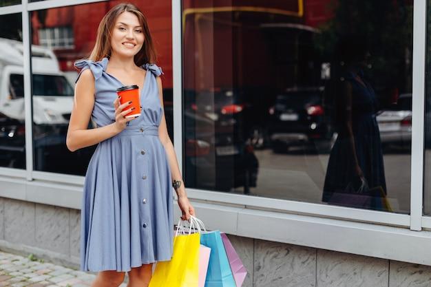 Piękna uśmiechnięta dziewczyna pozuje blisko centrum handlowego