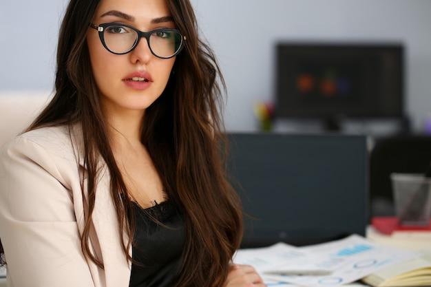 Piękna uśmiechnięta dziewczyna przy miejsca pracy spojrzeniem w kamerze