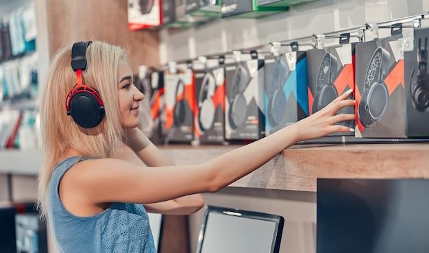 Piękna uśmiechnięta dziewczyna testuje nowe słuchawki w sklepie z elektroniką.