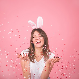 Piękna uśmiechnięta dziewczyna trzyma konfetti w rękach na białym tle nad różowym