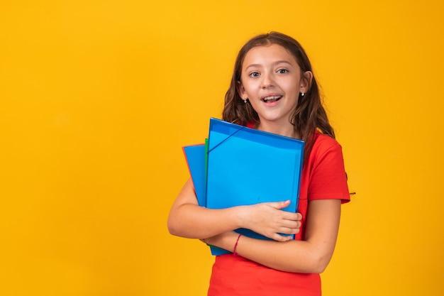 Piękna uśmiechnięta dziewczyna trzyma książkę idzie do szkoły. bliska portret, na białym tle żółte tło, dzieciństwo. dziecko przytulanie książki. styl życia, zainteresowania, hobby, czas wolny, czas wolny