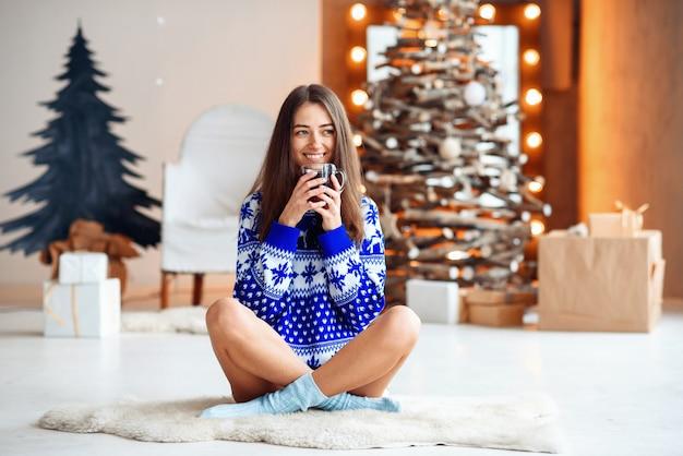 Piękna uśmiechnięta dziewczyna w ciepłym swetrze nowego roku siedzi na ciepłym białym dywanie