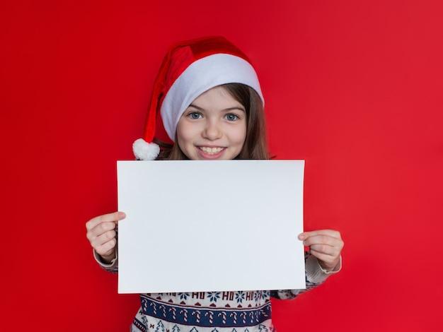 Piękna uśmiechnięta dziewczyna w koncepcji reklamy kapelusz świętego mikołaja na nowy rok i boże narodzenie