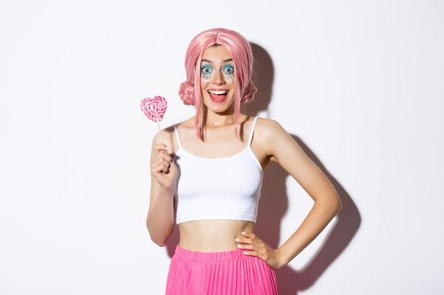 Piękna uśmiechnięta dziewczyna w różowej peruce, trzymająca cukierek w kształcie serca, cukierek albo psikus w stroju wróżki na halloween, stojąca.