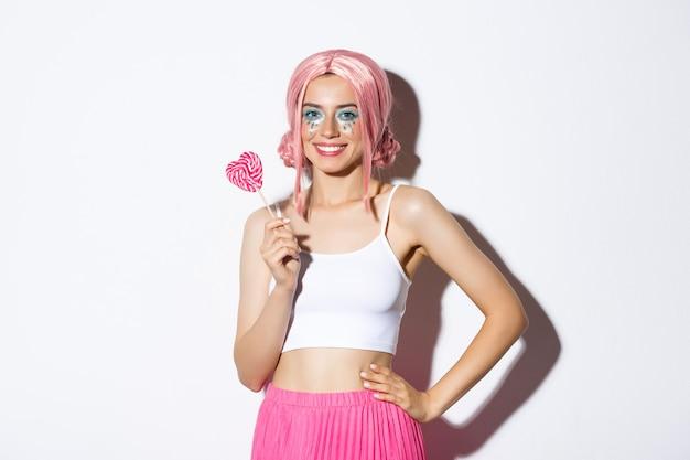Piękna uśmiechnięta dziewczyna w różowej peruce, trzymająca cukierki w kształcie serca, sztuczka lub leczenie w bajkowym kostiumie na halloween, stojąca na białym tle