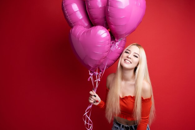 Piękna uśmiechnięta dziewczyna z balonami na czerwono
