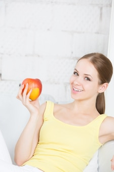 Piękna uśmiechnięta dziewczyna z jabłkiem siedzi w domu.