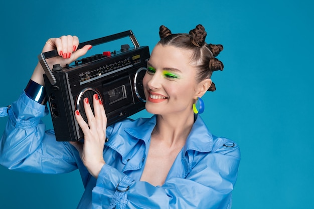 Piękna, uśmiechnięta dziewczyna ze stylowymi włosami i makijażem posiada boombox