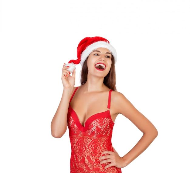 Piękna, uśmiechnięta i emocjonalna dziewczyna w świątecznym stroju kąpielowym. emocjonalna kobieta w czerwonym santa claus kapeluszu odizolowywającym na bielu. wesołych świąt bożego narodzenia i nowego roku