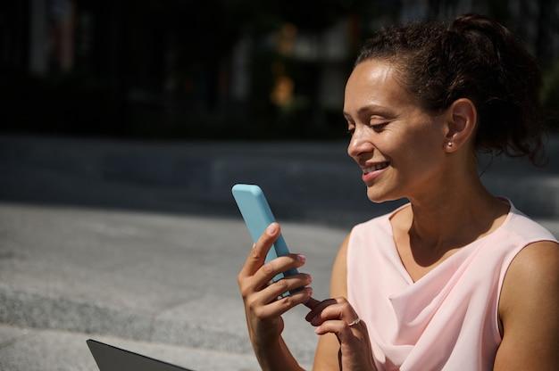 Piękna uśmiechnięta kobieta african american przesuwając na smartfonie. atrakcyjna wesoła kobieta rasy mieszanej używa telefonu komórkowego na zewnątrz