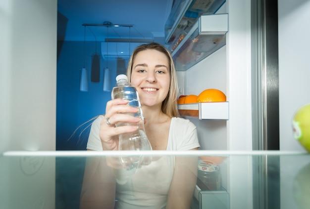 Piękna uśmiechnięta kobieta biorąc wodę z lodówki i pijąc ją. widok z wnętrza otwartej lodówki