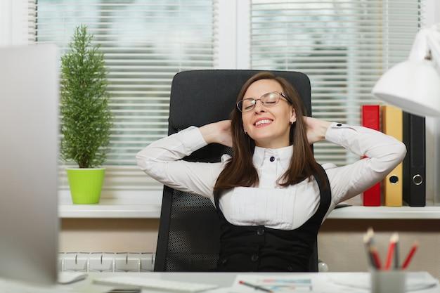Piękna uśmiechnięta kobieta biznesu brązowe włosy w garniturze i okularach siedzi przy biurku i relaks po pracy przy komputerze z nowoczesnym monitorem z dokumentami w jasnym biurze, patrząc w kamerę.