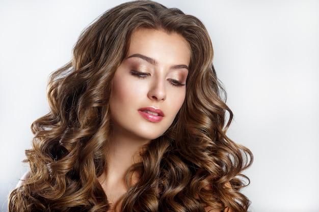 Piękna uśmiechnięta kobieta brunetka dziewczynka o długich, lśniących falowanych włosach i makijażu