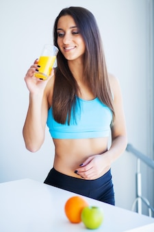 Piękna uśmiechnięta kobieta, ciesząc się szklanką soku pomarańczowego rano.