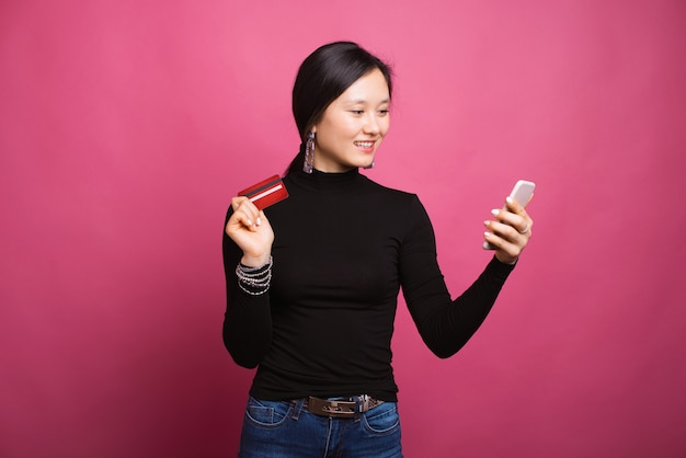 Piękna uśmiechnięta kobieta jest przyglądająca jej telefon robi zakupy online płacący z jej kartą.