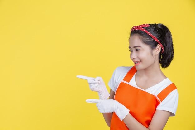 Piękna uśmiechnięta kobieta jest ubranym żółte gumowe rękawiczki na kolorze żółtym.